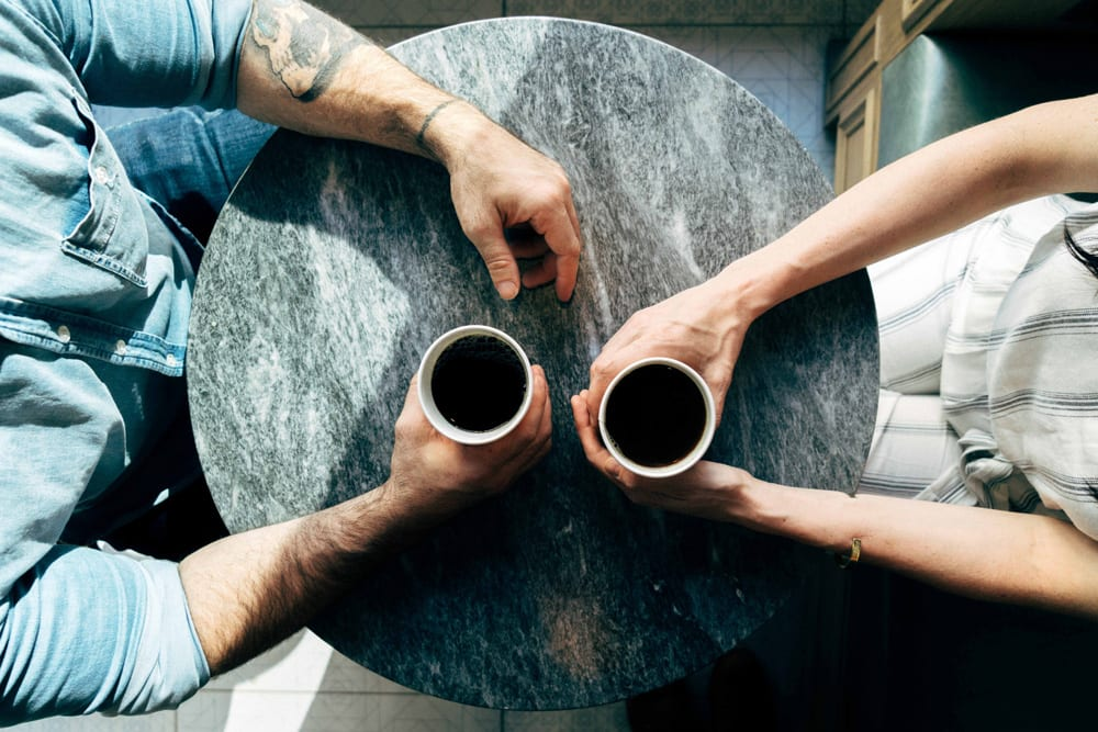 A photo shot from above of two people drinking coffee and talking at a table